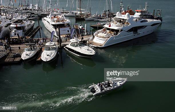 A motor launch passes the new Sunseeker yacht the Predator 130 which is on display on the first day of the PSP Southampton Boat Show in Mayflower...