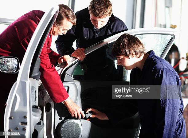 motor mechanical engineer teaching students in garage - hugh sitton photos et images de collection
