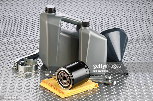 Motor oil canisters with tools on diamond plate background