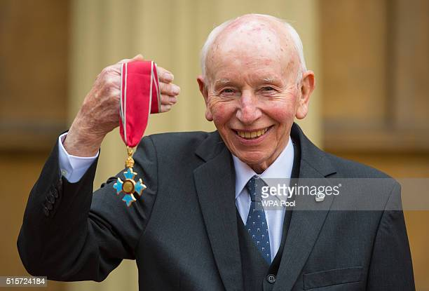 Motor racing legend John Surtees with his Commander of the Order of the British Empire medal which was awarded by the Duke of Cambridge at an...