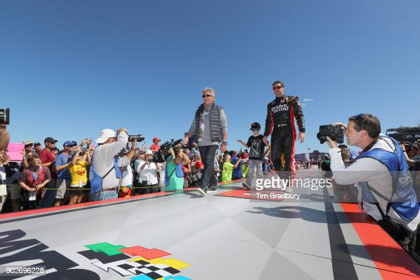 Motor racing legend Mario Andretti and driver Elliott Sadler driver of the Golden Corral Chevy walk the driver's intros before 59th Annual DAYTONA...