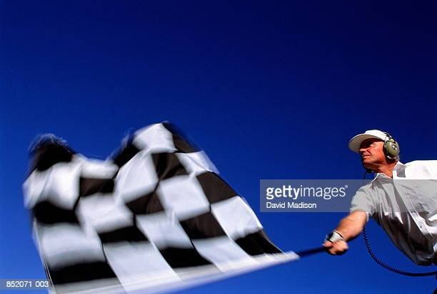 Motor racing, official waving chequered flag (blurred motion)