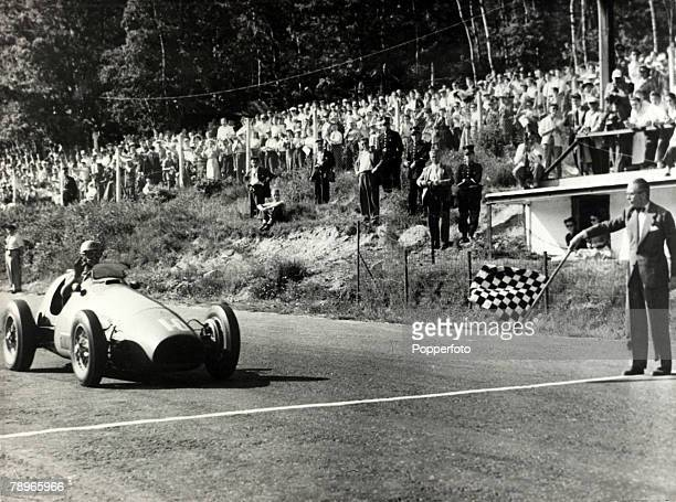23rd June 1953 Italian motor racing ace Alberto Ascari takes the chequered flag to win the Belgian Grand Prix at Francorchamp Alberto Ascari 19181955...