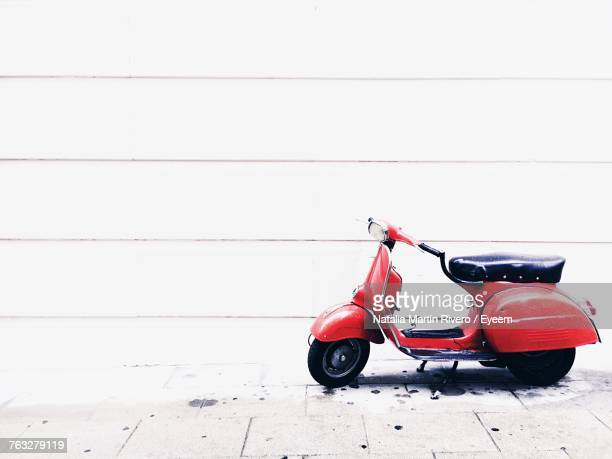 motor scooter parked against wall - moped stock photos and pictures