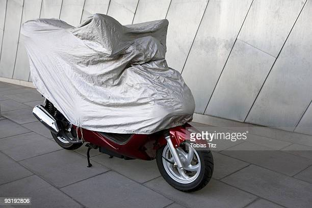 A motor scooter under a protective cover