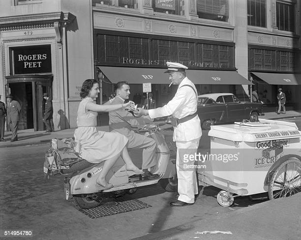 Motor scootering around New York City as part of their $300 honeymoon Denise and Antoine Baud of Paris buy an ice cream bar from Good Humor Man Sotir...