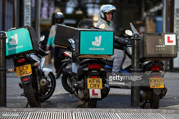 Motor scooters with boxes for Deliveroo operated by Roofoods Ltd left and center stands next to a motor scooter with a box for UberEats operated by...