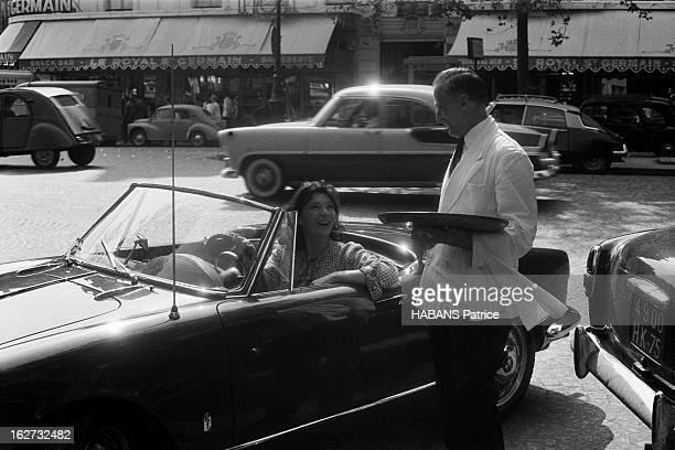 Juliette Greco Juliette GRECO au volant de sa voiture décapotable Alfa Romeo Giulietta discutant avec le garçon du café de Flore à SaintGermaindesprés