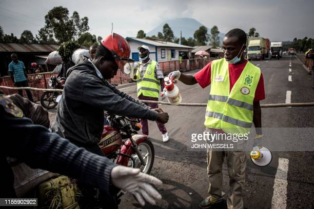 TOPSHOT A motor taxi driver gets his hands washed at an Ebola screening station on the road between Butembo and Goma on July 16 2019 in Goma The...