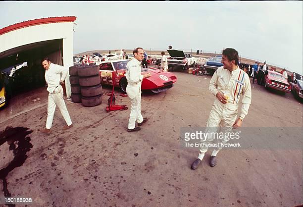 Motor Trend 500 NASCAR Riverside Bobby Allison talks to other drivers in the paddock Bobby Allison's Dodge Daytona sits to the left