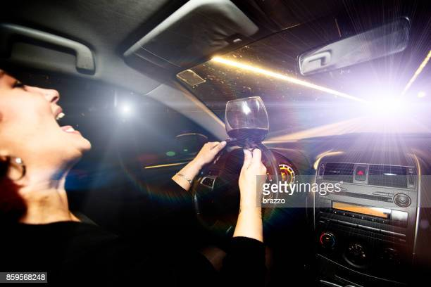motor vehicle driver drives a car holding a glass of wine - drunk woman stock pictures, royalty-free photos & images