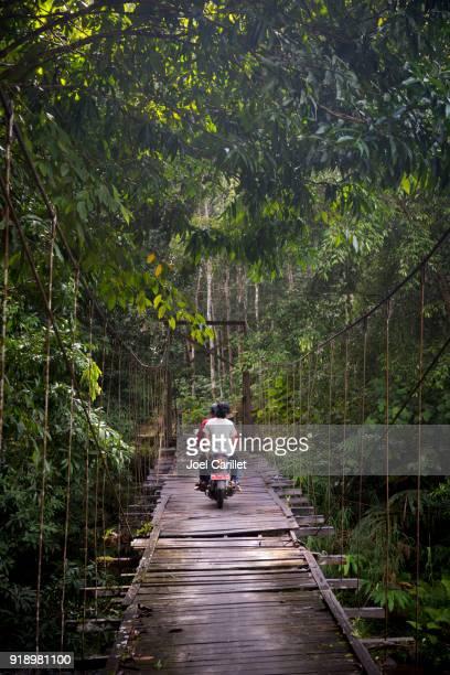 Motorbike crossing worn bridge near Loksado, South Kalimantan, Indonesia