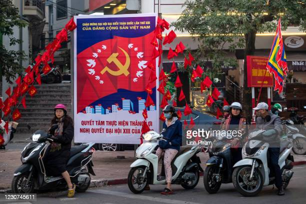 Motorbike drivers wait for traffic light near a poster for the upcoming 13th National Congress of the Communist Party of Vietnam on January 23, 2021...