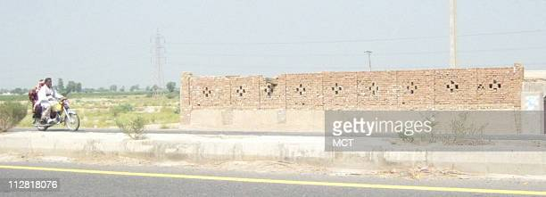 A motorbike drives past the arched gates of the new JaisheMohammad compound in Bahawalpur Pakistan