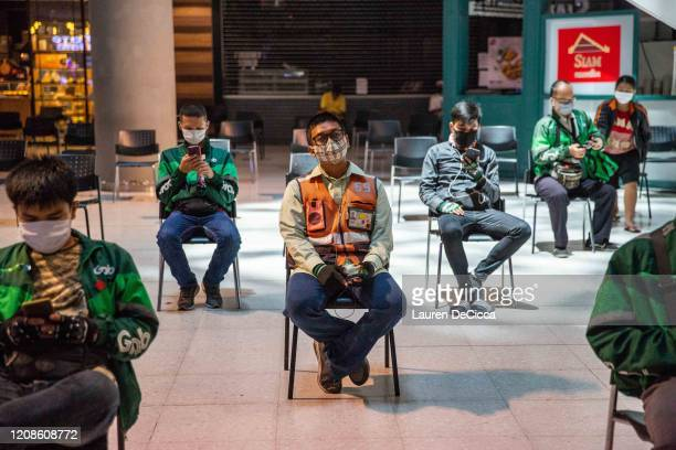 Motorbike food delivery drivers wait to pick up orders in organized social distancing chairs in Central Plaza Pinklao Mall on March 30 2020 in...
