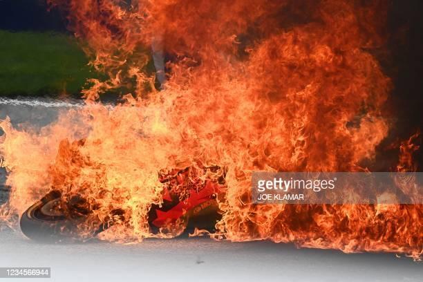 Motorbike is seen on fire following a crash involving Aprilia Italian rider Lorenzo Savadori and KTM Spanish rider Dani Pedrosa after the start of...