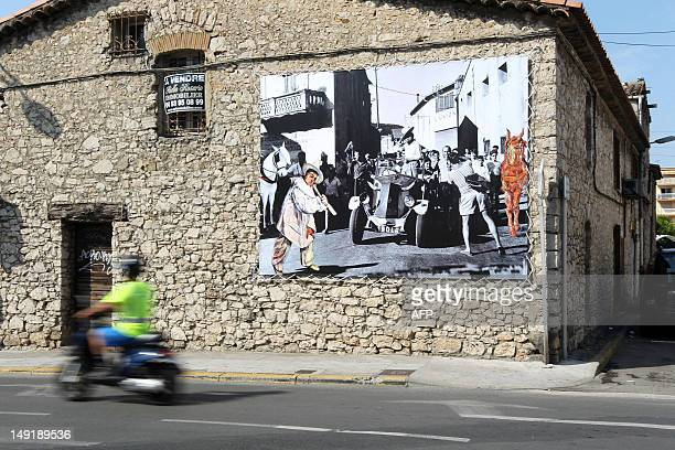 A motorbike passes by a photograph showing Spanish artist Pablo Picasso on July 24 2012 in the street of the eastsouthern city of Vallauris These...