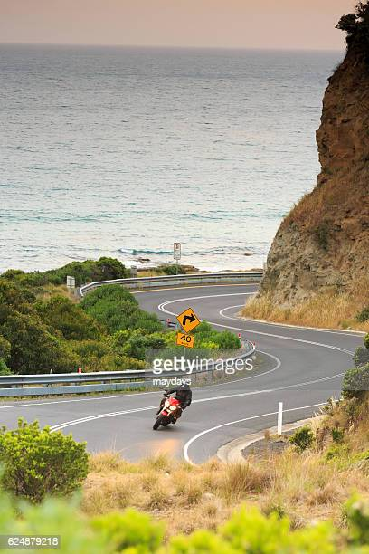 A Motorbike rider next to the Ocean, great ocean road, Victoria, Australia, South Pacific