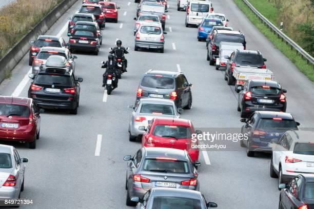 motorrijders inhalen de voertuigen in verkeer jam - passeren stockfoto's en -beelden