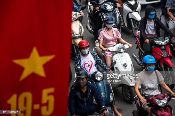 Motorbike riders with face masks are stuck in traffic during the morning peak hour on May 19, 2020 in Hanoi, Vietnam. Though some restrictions remain...