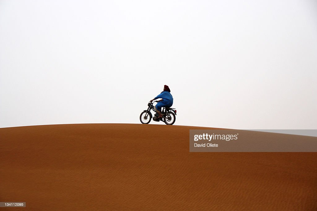 Motorbike running on desert dune : Stock Photo