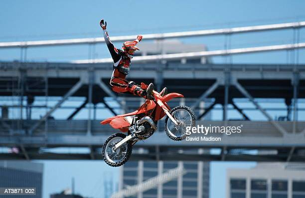 Motorbike stunt rider in mid-air, low angle view (Enhancement)