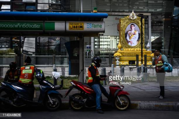Motorbike taxi drivers locally known as motorsai wait for passengers near a portrait of Thailand's King Maha Vajiralongkorn in Bangkok on May 1 ahead...
