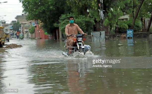 Motorbiker drives through a flooded street after heavy rainfall hit Pakistan's Rawalpindi on May 14, 2020.