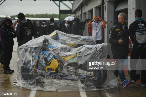 Motorbikes are seen with waterproof covers on as the start of the MotoGP race is delayed due to rain during the motorcycling British Grand Prix at...