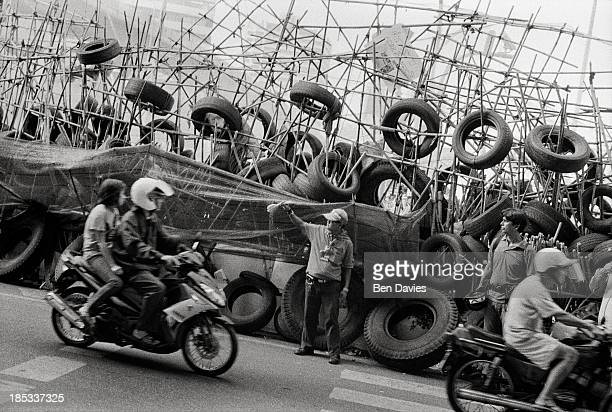Motorbikes drive past a makeshift Red Shirt barricade constructed outside Lumpini Park in the commercial heart of Bangkok during a prolonged series...
