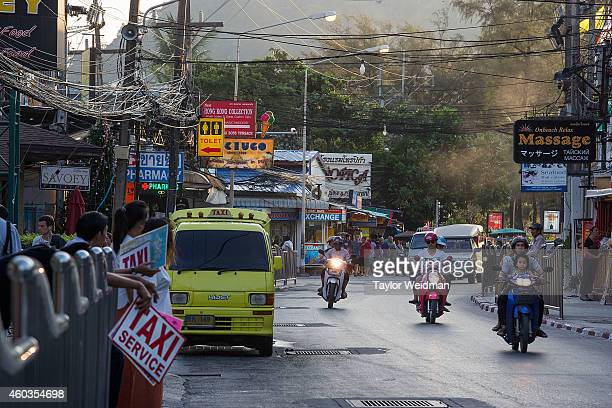 Motorbikes, vans, cars, and taxis travel along a busy Patong road running parallel to the beach on December 10, 2014 at Patong Beach in Phuket,...