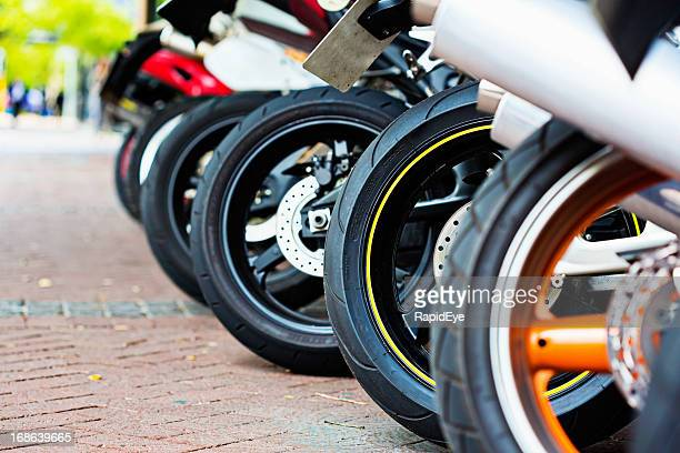 Motorbikes with a variety of tyres lined up on forecourt