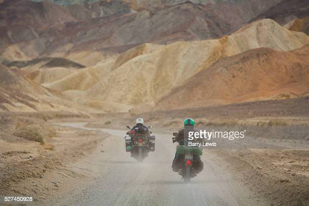 Motorbikes with camping gear on 20 mule team road in Death Valley National Park in California noted for its erosional landscape and being one of the...