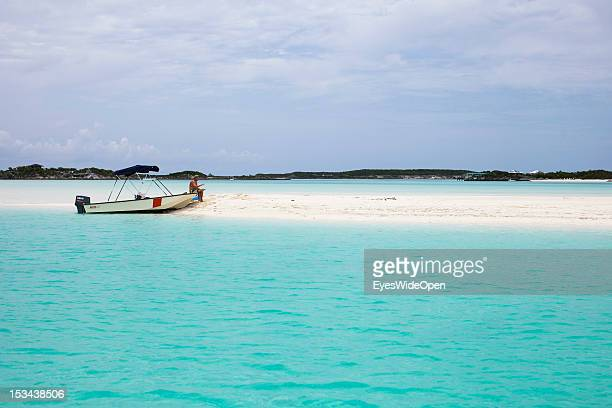 Motorboat and a man are at a white sand stripe in the turquois carribean sea at Compass Cay Marina on June 15 2012 in the Islands of the Exumas The...