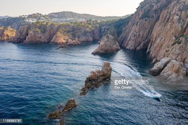 lancha motora en los acantilados de la costa brava al atardecer. españa - provincia de gerona fotografías e imágenes de stock