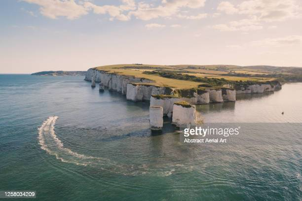motorboat rounding old harry rocks photographed from a drone, dorset, england, united kingdom - rock stock pictures, royalty-free photos & images