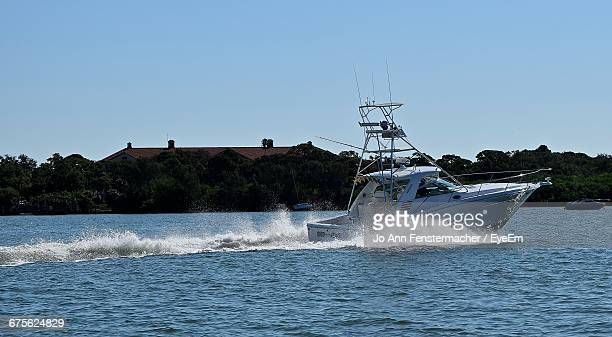 motorboat sailing in sea against clear blue sky - costa del golfo degli stati uniti d'america foto e immagini stock