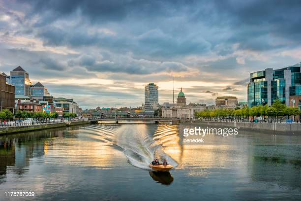 motorboat speeding on river liffey dublin ireland - dublin stock pictures, royalty-free photos & images