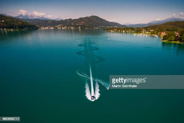 motorboot mit wasserskifahrer am wörthersee - waterskiing stock photos and pictures