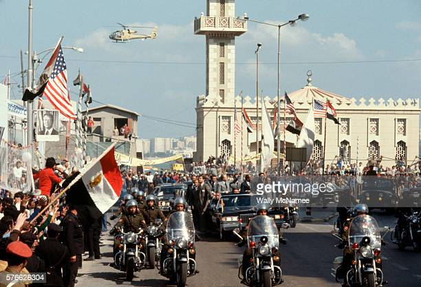 A motorcade led by motorcycle police travels the packed parade route through Alexandria Egypt on the occasion of US President Jimmy Carter's visit in...