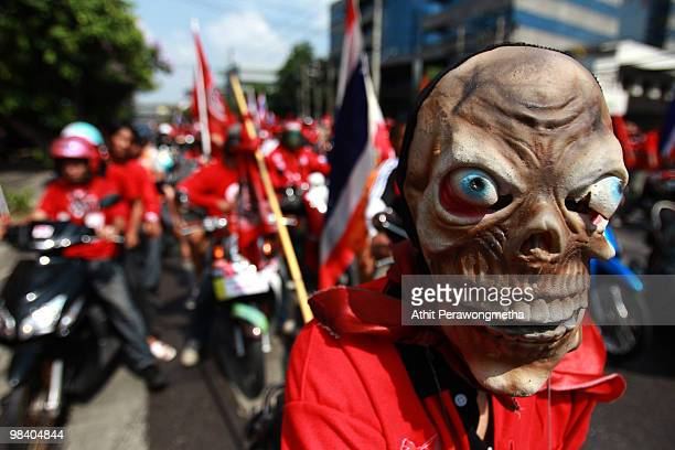 A motorcade of Red Shirt supporters of former Prime Minister Thaksin Shinawatra gather during a funeral procession for the victims of clashes between...