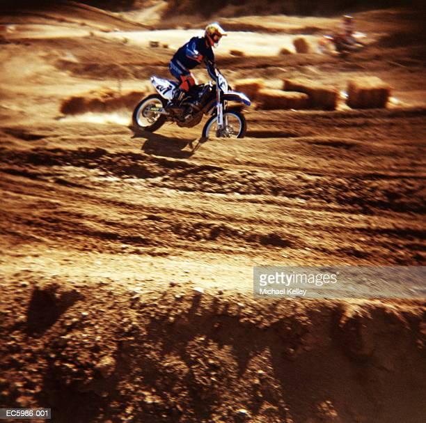 Motorcross biker riding on dirt road