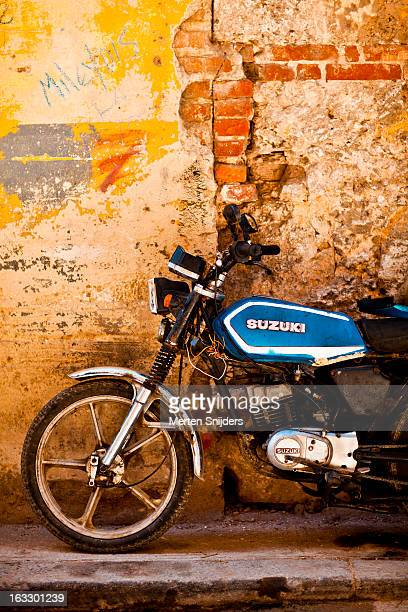 motorcycle against eroded wall - merten snijders stock pictures, royalty-free photos & images