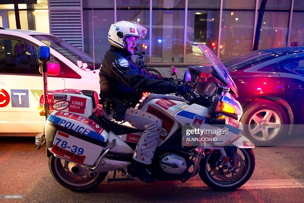 A motorcycle cop wearing casual trousers stands parked on a street November 04, 2014 in Montreal to protest the Quebec provincial government proposal to reduce costs of municipal pensions by having workers contribute more toward their retirement.