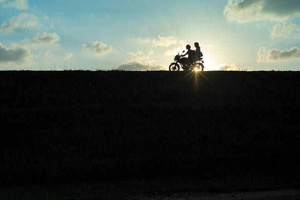 Motorcycle couple silhouetted at sunset