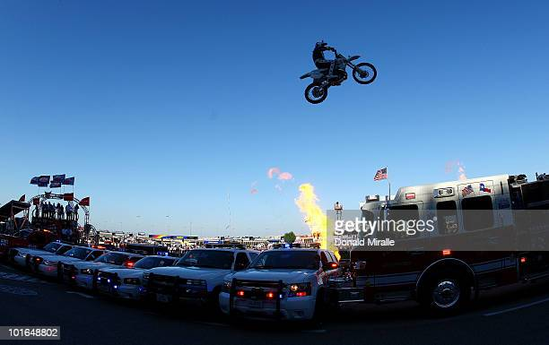 Motorcycle daredevil Robbie Knievel jumps a line of police cars ambulances and a fire truck spanning 200 feet in his 'Above the Law' jump prior to...