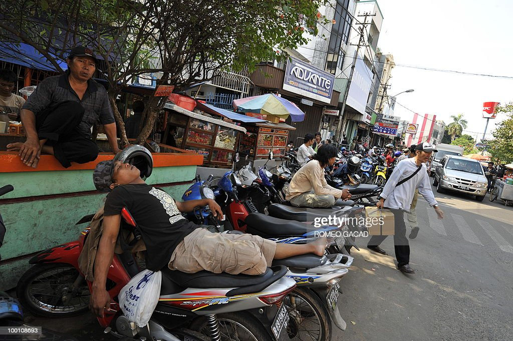 Motorcycle drivers wait for passengers in Glodok district in Jakarta on May 21, 2010. Glodok a predominantly ethnic Chinese business district was razed and looted during bloody anti-Chinese riots during the downfall of Indonesian military strongman Suharto in 1998. Twelve years after the dawning of Indonesia's 'Reformasi' movement with the Suharto's resignation there are fears the country of 240 million people is on a slipperly slope backwards.