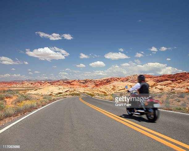 Motorcycle driving on desert highway.