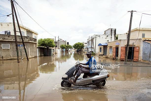 Motorcycle is seen in a flooded street after torrential rain in Pikine district of Dakar, Senegal on August 12, 2016. Citizens try to live in hard...