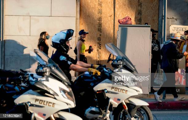 LAPD motorcycle officers drive past protesters during a demonstration over the death of George Floyd while in Minneapolis Police custody in downtown...
